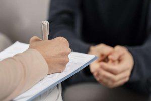 Terapeuta tomando nota a un paciente por maltrato psicológico familiar
