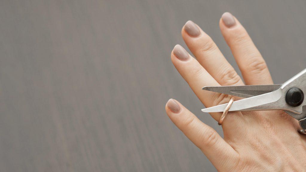 Mujer cortando su alianza de casada para divorciarse. Necesita acudir a psicólogos matrimoniales Móstoles.