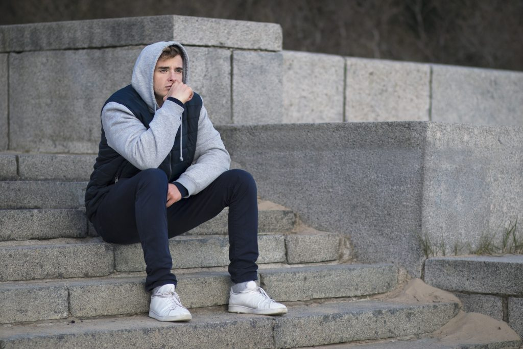 Chico sentado en unos escalones triste. Necesita tratamiento de depresión y ansiedad