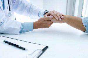 Psicólogo ofreciendo psicooncología como tratamiento contra el cáncer a un paciente mientras le coge la mano