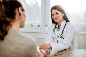 Doctora le coge la mano a una paciente para darle ánimos en clínica psicooncología